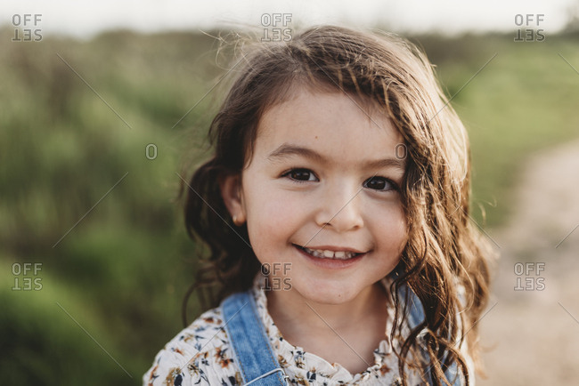 Portrait of young school-aged girl with brown eyes smiling at camera