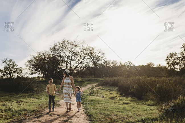Front view of mother, son, and daughter walking in sunny field