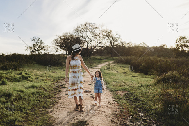 Front view of mother and daughter walking while looking at each other