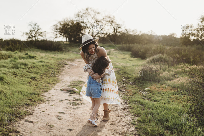 Young mother and young girl hugging in backlit meadow