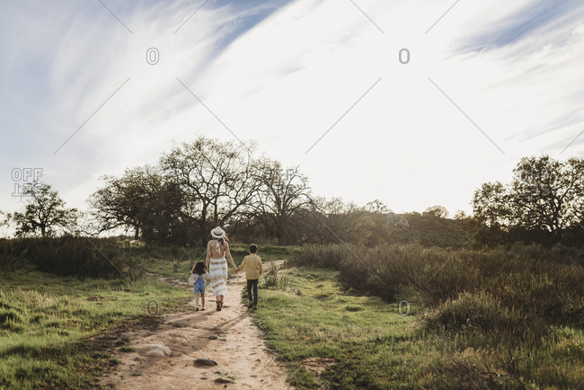 Young mother, son, and daughter holding hands while walking away