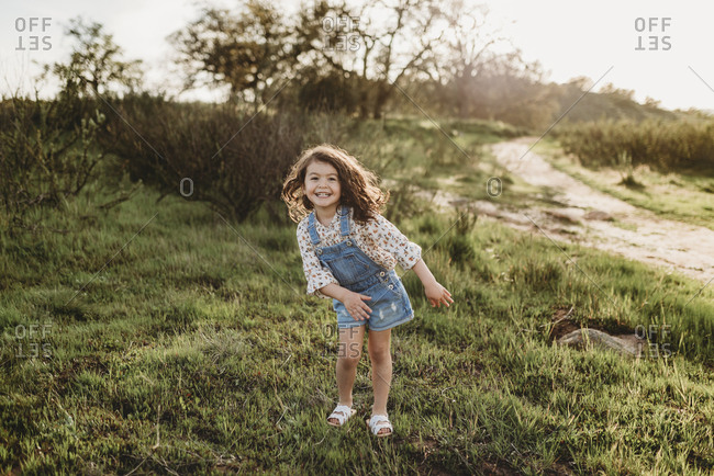 Full length view of young school-aged girl dancing in backlit field