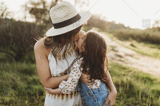 Young mother with hat and daughter kissing in backlit meadow