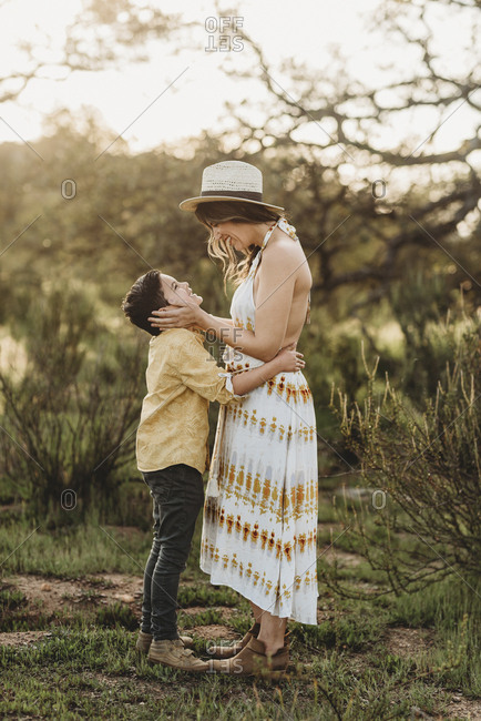 Side view of mother and son in backlit field looking at each other