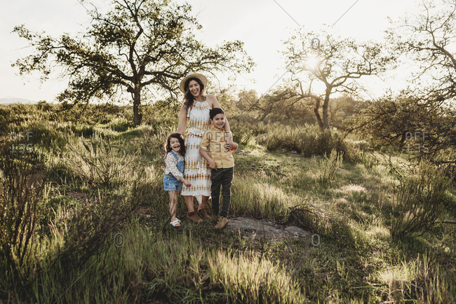 Portrait of beautiful mother and young children in sunny field