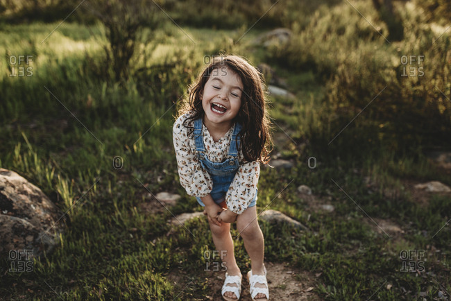 Young school-aged girl with sunlight in her hair laughing