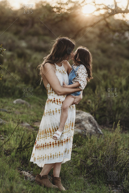 Full length view of mother and daughter kissing in sunny field