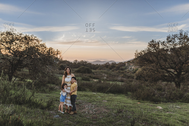 Landscape of young mother and children smiling under blue sky in field