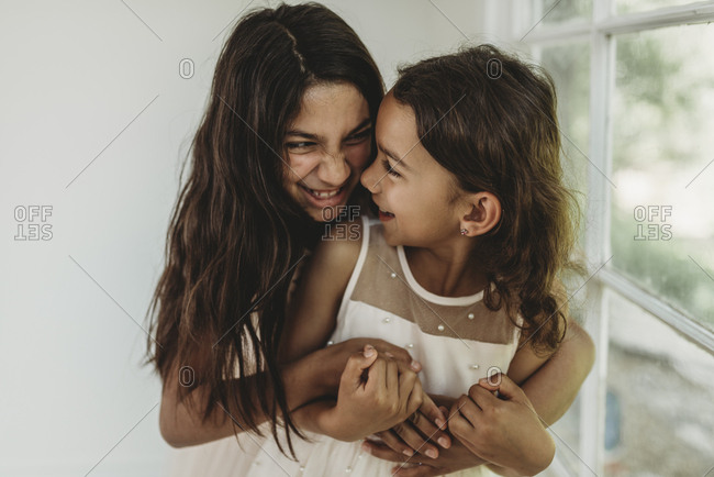 Sisters hugging in natural light studio while looking at each other