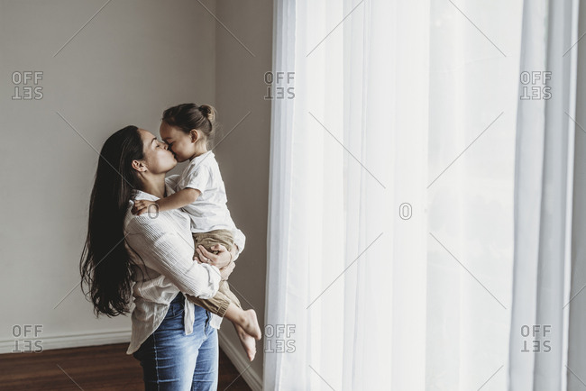 Young mother with long hair holding toddler boy and kissing in studio