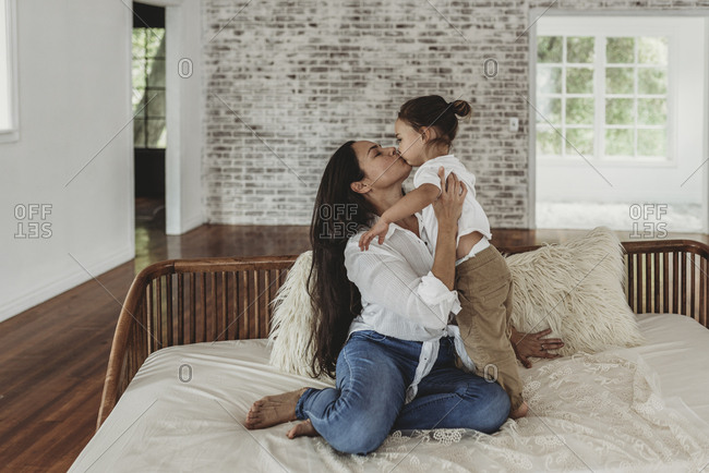 Young mother kissing toddler boy on couch in natural light studio