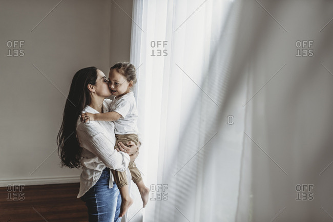 Side view of young mother holding toddler boy in embrace and kissing