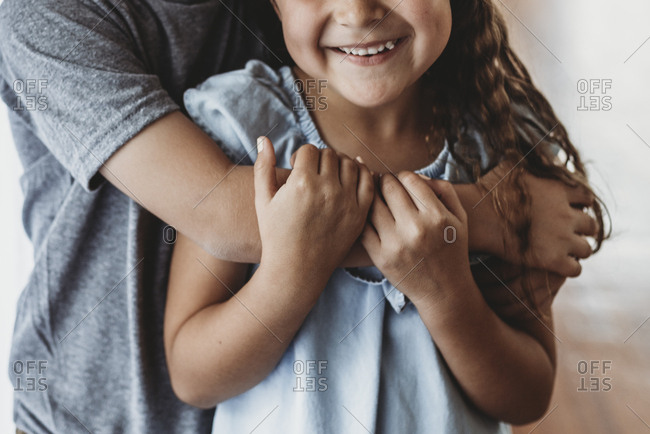 Close up image of brother embracing sister and sister smiling