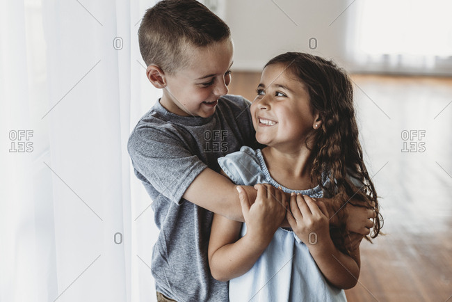 Brother and sister laughing at each other in natural-light studio