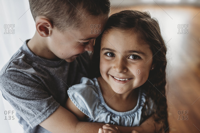 Portrait of young girl while brother embraces her and laughs
