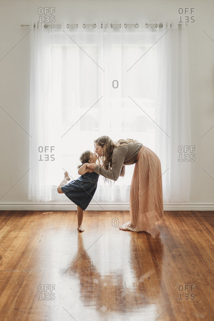 Mother bending down to give daughter a kiss