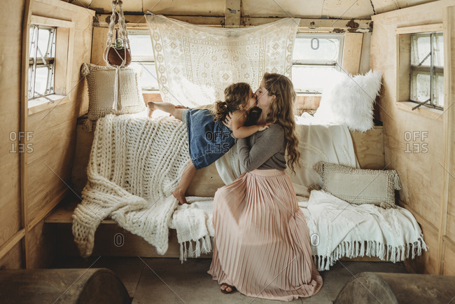 Mother and daughter kissing in boho studio setup