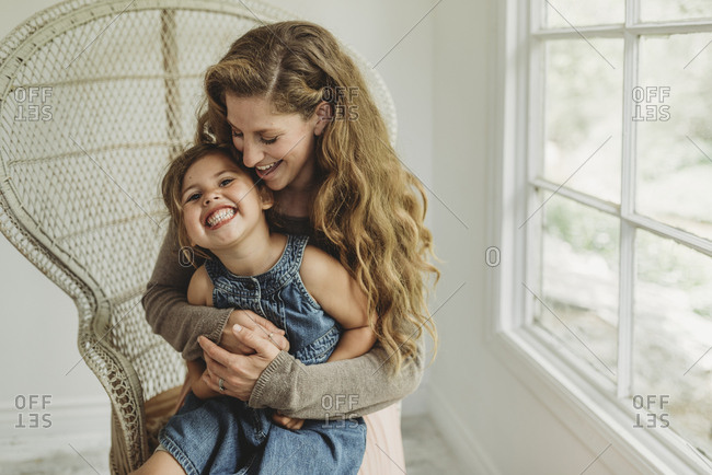 Daughter being held by Mother in boho chair and smiling in studio