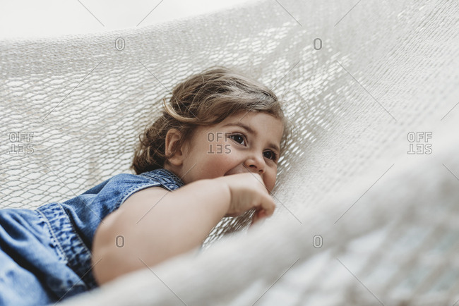 Young preschool aged girl resting in hammock looking away