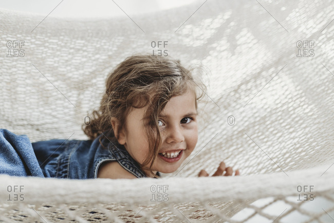 Young girl in hammock in studio smiling and looking at the camera