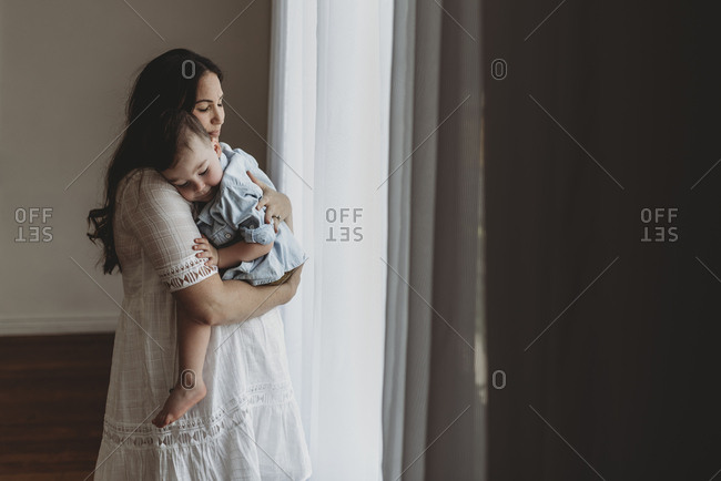 Young pregnant mother cuddling with young son in natural light studio