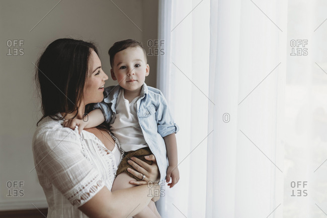 Side view of mother looking at toddler son in natural light studio