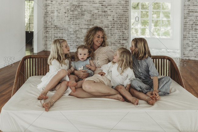 Mother and daughters looking at each other lovingly on studio couch