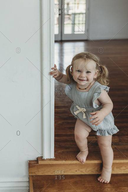 Toddler girl smiling at camera while walking down stairs in a studio