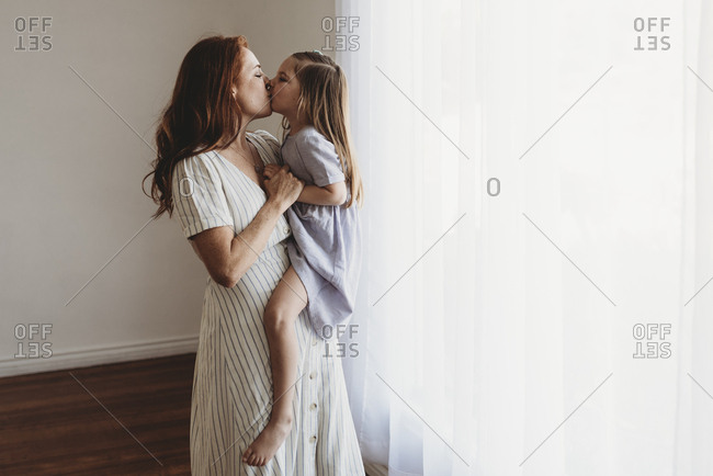 Side view of young mother holding daughter and kissing in studio