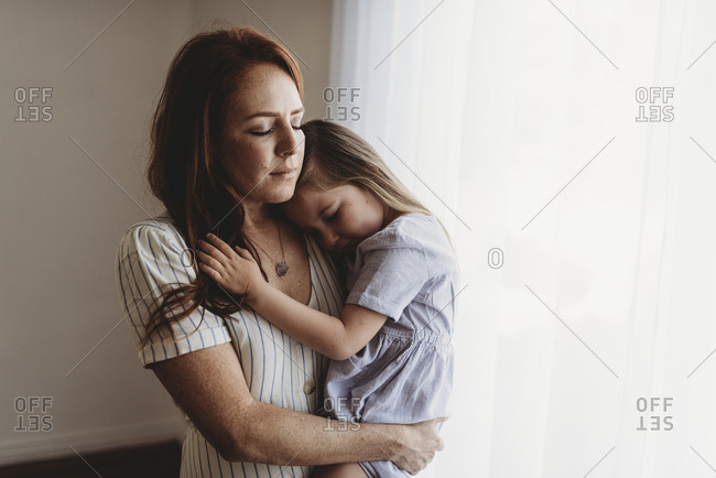 Young mother cuddling with young daughter while closing eyes in studio