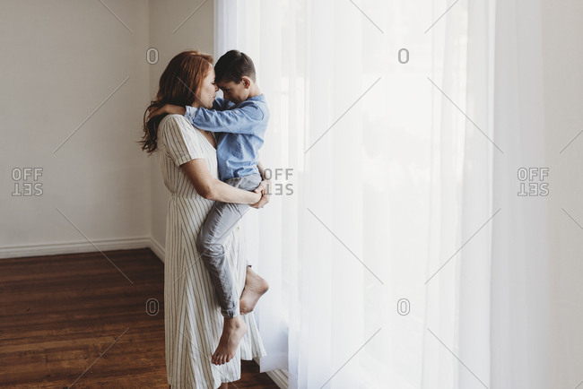 Side view of young mother holding school-aged son in studio