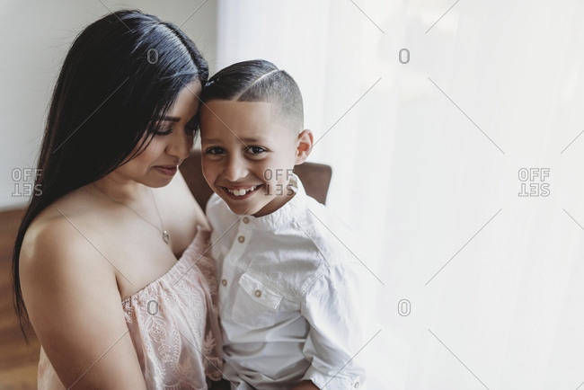 Side view of mother embracing son while he smiles at camera