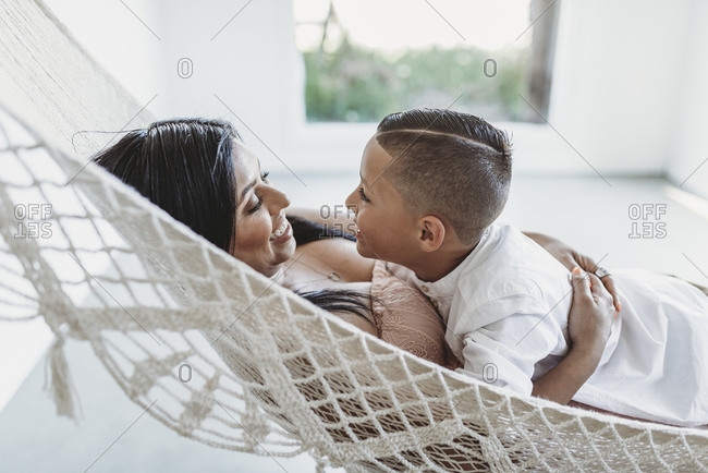 Mother and young son looking at each other while laying in hammock
