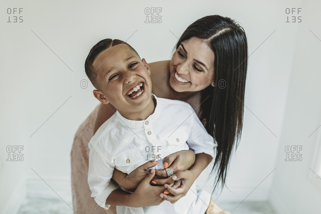 Mother hugging son from behind and looking at him in studio