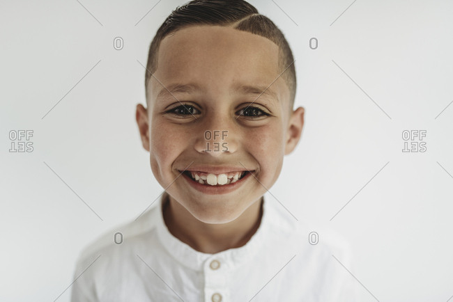 Portrait of young school-aged boy smiling in studio