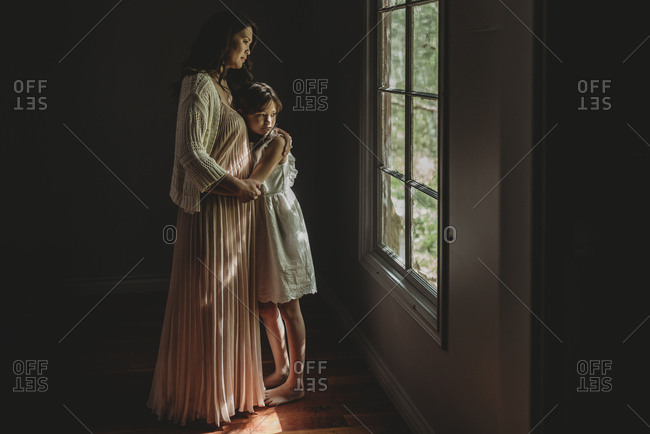 Mother and daughter embrace and looking out studio window