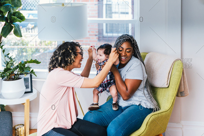 Cheerful mothers playing with cute baby boy in living room at home
