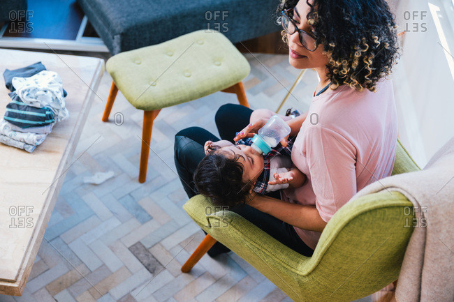 High angle view of mother feeding milk to cute son with baby bottle while sitting in living room