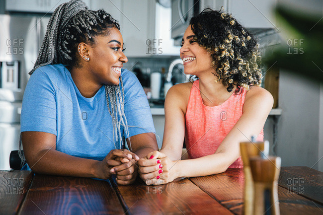 Cheerful lesbian couple looking each other face to face while sitting at table
