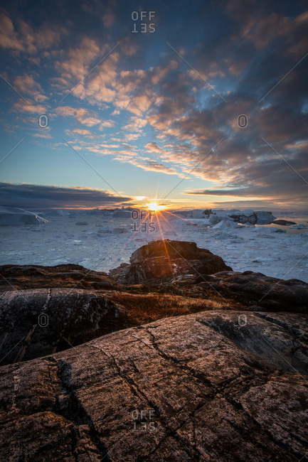Icebergs floating off rocky shore in the ocean at sunset