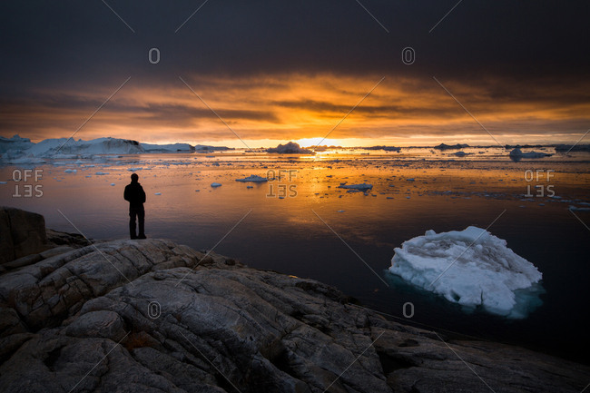 Person overlooking icebergs floating off shore in the ocean at sunset