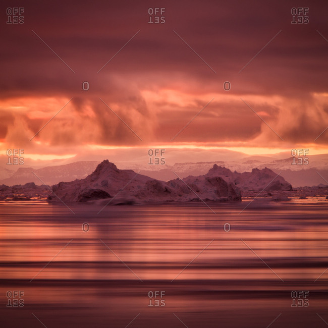 Icebergs floating in the ocean at sunset