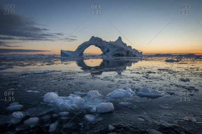 Lone iceberg floating in the ocean at sunset