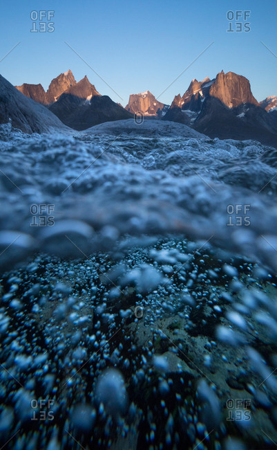 Underwater view of rushing stream with mountains above, Greenland