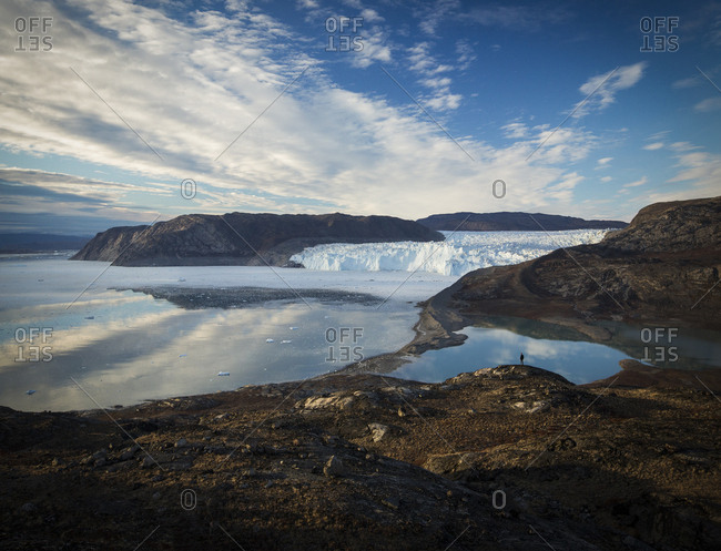 Peron exploring rocky shoreline overlooking glacier; Basalt coastline, Greenland