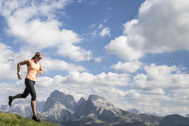 A woman trail runner charges in front of a Dolomites mountainscape