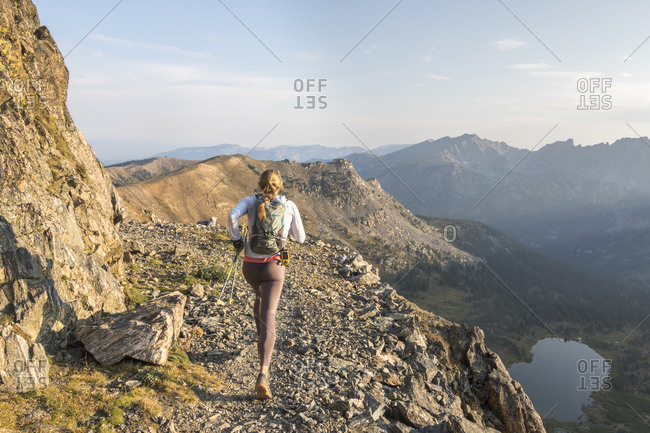 A young woman enjoys an early morning trail run high up in the Rocky M