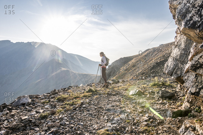 A young woman trail runner takes a break high up on Arapaho Pass