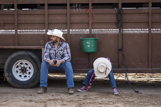 United States, Arizona, Chandler - March 9, 2019: A father and son rest before the Arizona Black Rodeo begins