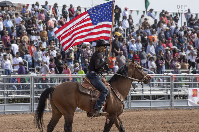 United States, Arizona, Chandler - March 9, 2019: A rider carries an American flag opening the Arizona black rodeo